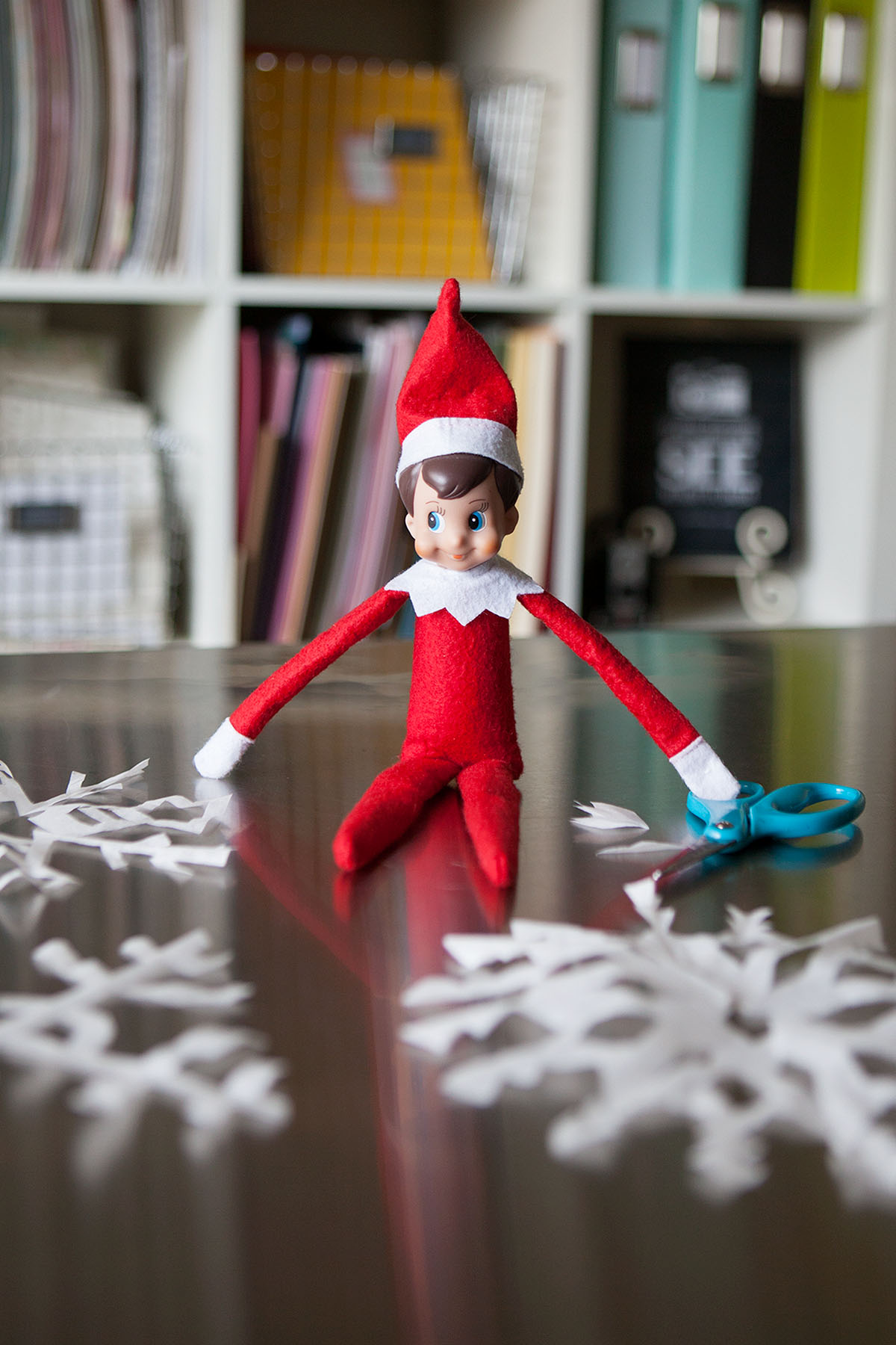 Elf makes paper snowflakes.
