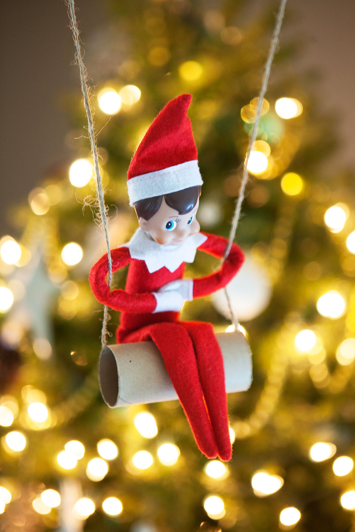 Elf swings by the tree.