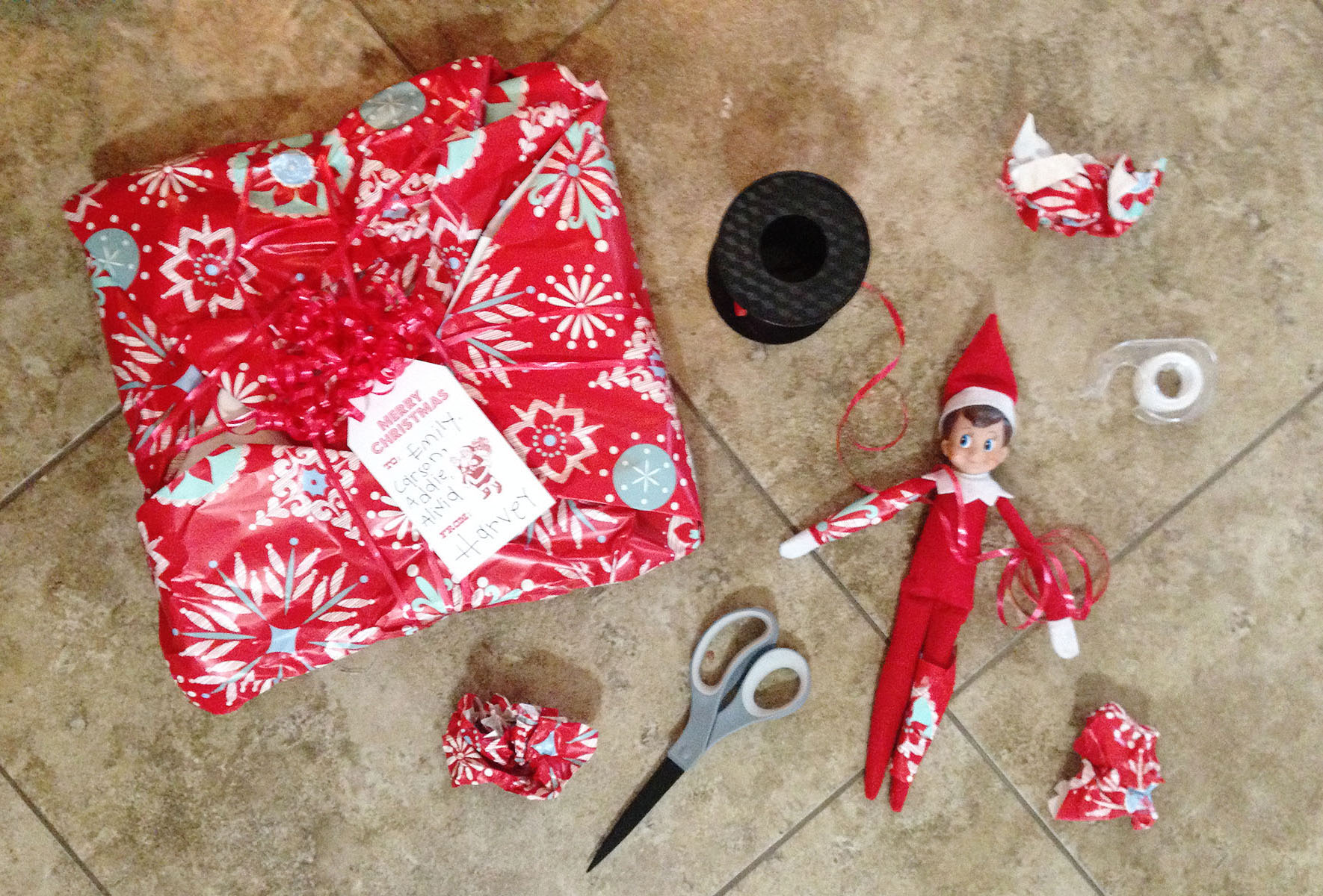 Elf makes a mess while trying to wrap presents.