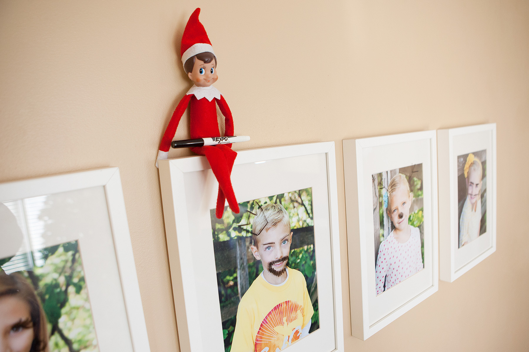 Elf draws silly faces on framed photos with dry erase marker.