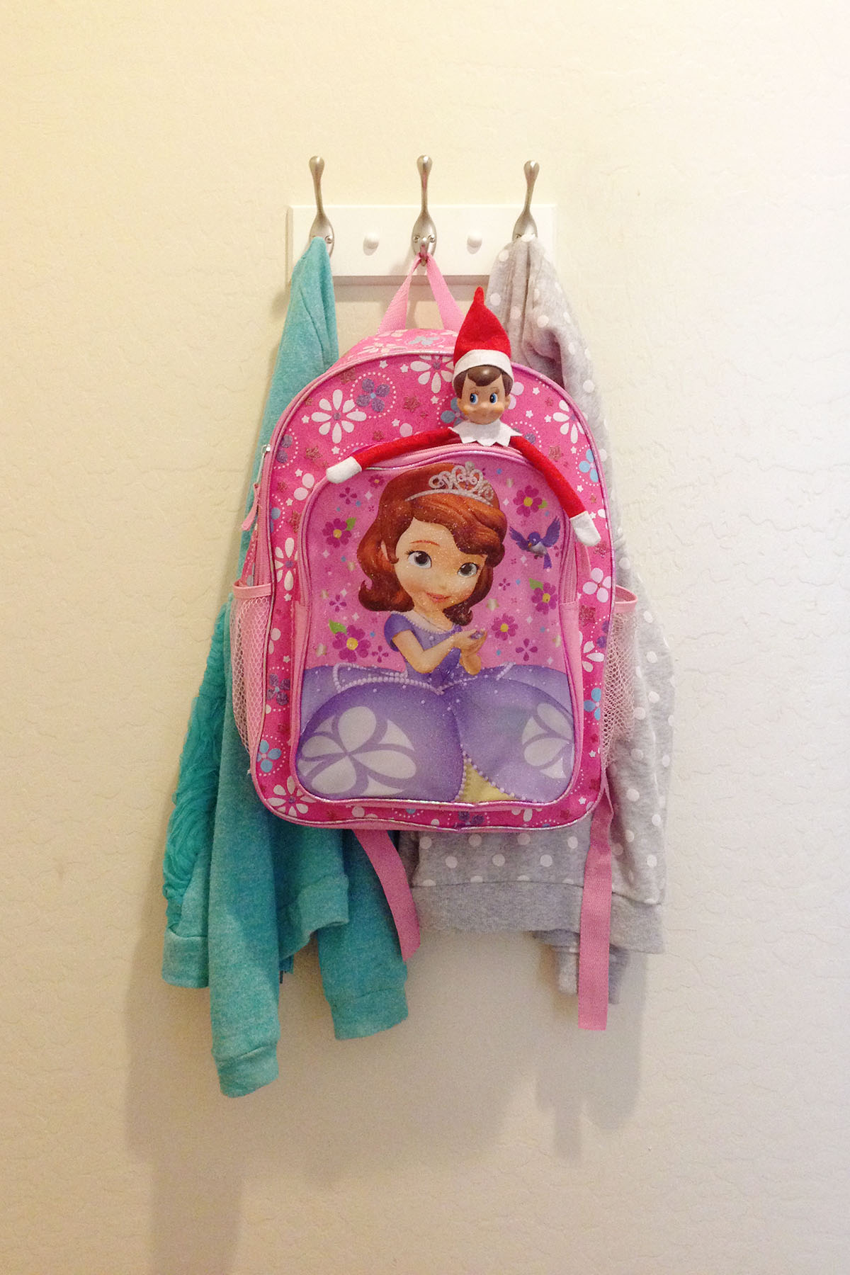 Elf hides in a child's backpack for them to find on their way out the door to school.