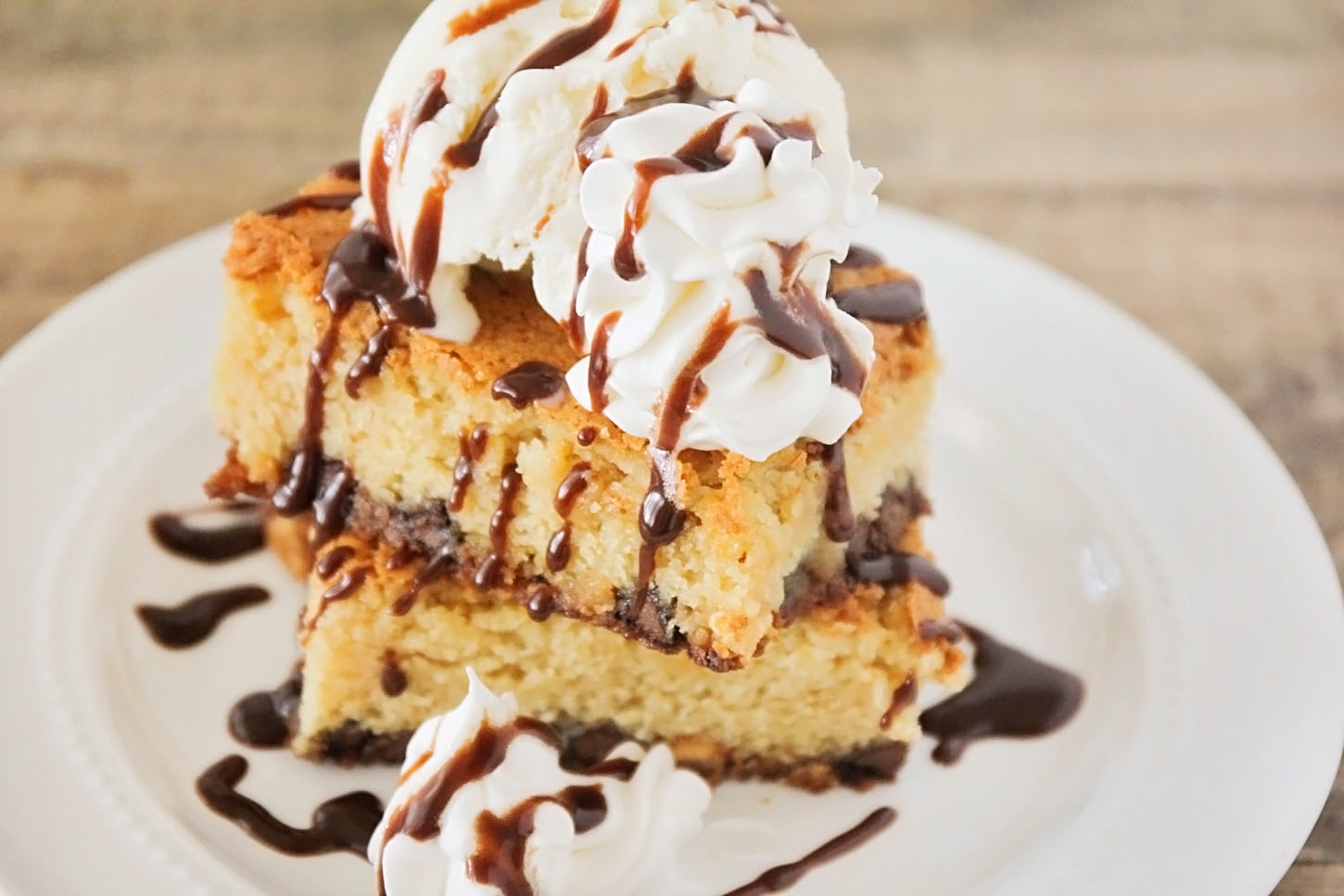 White chocolate blondies scattered with chunks of milk chocolate topped with ice-cream, homemade chocolate sauce and whipped cream!