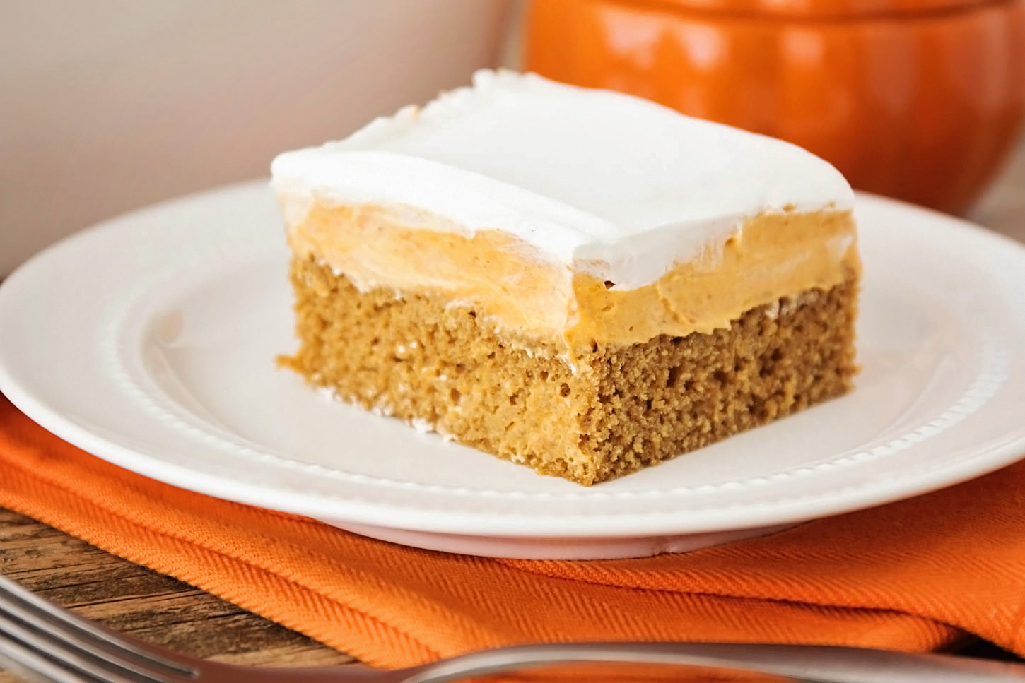 Delicious layers of soft gingerbread cake, creamy pumpkin filling and light whipped topping in an easy to make fall dessert.